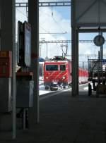 die grose Bahn/241/ein-bahnsteigbild---so-wie-der Ein Bahnsteigbild - so wie der auf den Zug wartenden Reisende die Bahn sieht und erlebt: Entwerter und Fahrplan, Zeit und Gepäckhandwagen sind in diesem Augenblick bedeutungslos im Schatten, was zählt, obwohl nur bruchstückweise sichtbar ist der einfahrende Zug... Disentis, den 22. März 2008